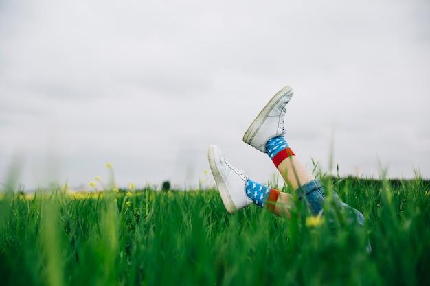 Jambes en chaussures blanches et au-dessus de l'herbe Photo gratuit
