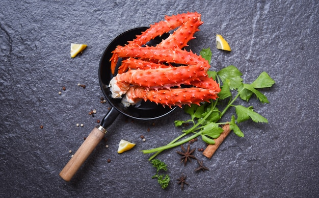 Jambes de crabe en pot sur fond sombre alaska king crabe hokkaido fruits de mer cuit herbes et épices au citron Photo Premium