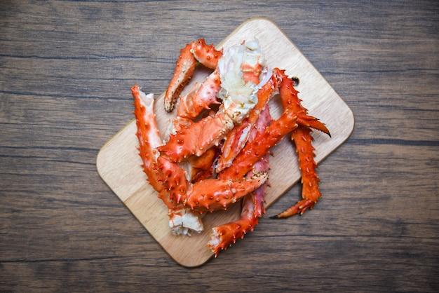 Jambes de crabe roi d'alaska cuites de fruits de mer sur fond de planche à découper en bois - crabe rouge hokkaido Photo Premium