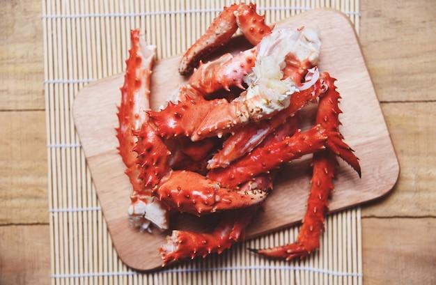 Jambes de crabe roi d'alaska cuites de fruits de mer sur une planche à découper en bois - hokkaido au crabe rouge Photo Premium