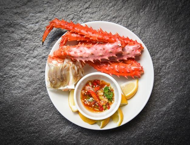 Jambes de crabe royal d'alaska cuites de fruits de mer avec sauce au citron sur une assiette blanche Photo Premium