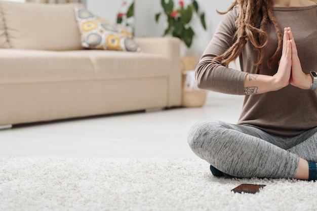 Jambes Croisées De Jeune Femme Active Gardant Ses Mains Jointes Par La Poitrine Alors Qu'il était Assis Sur Le Sol à La Maison Photo Premium