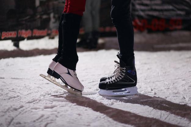 Jambes du couple de baisers amoureux sur des patins. Photo Premium