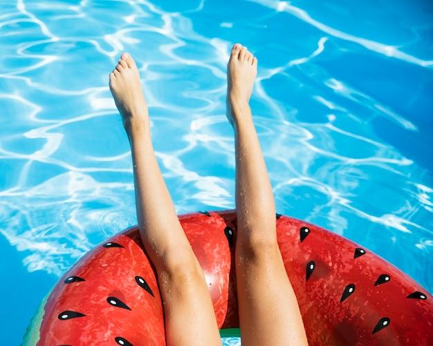 Jambes à l'envers avec floatie melon d'eau Photo gratuit