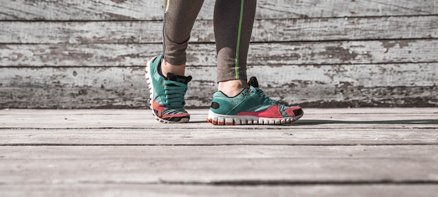 Jambes Féminines En Collants Et Chaussures De Sport Sur Fond De Bois, Concept Sports Photo gratuit