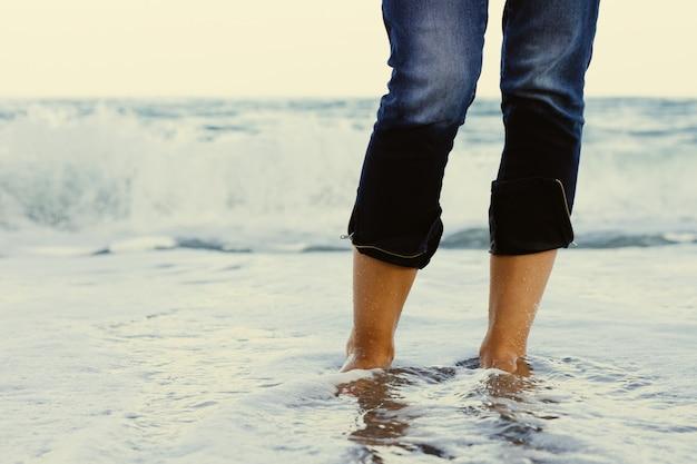 Jambes féminines en jeans debout dans l'eau de mer sur le fond d'une vague déferlante Photo Premium