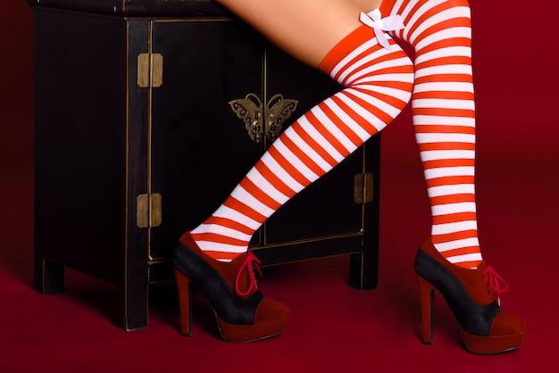 Jambes de femme avec des collants à rayures rouges et blanches sur fond rouge Photo gratuit