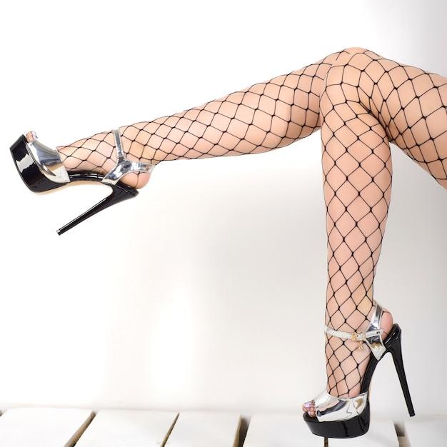 Jambes De Femme Portant Des Bas Résille Et Des Chaussures D'argent Talons Hauts Photo Premium