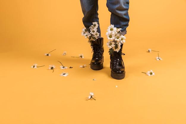 Jambes de femme portant des chaussures avec des fleurs à l'intérieur Photo gratuit