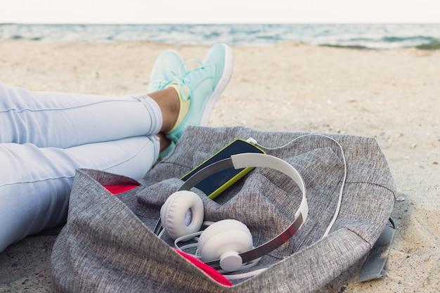 Jambes de femmes en jeans et baskets, sac à dos, casques et téléphone intelligent sur la plage en été Photo Premium