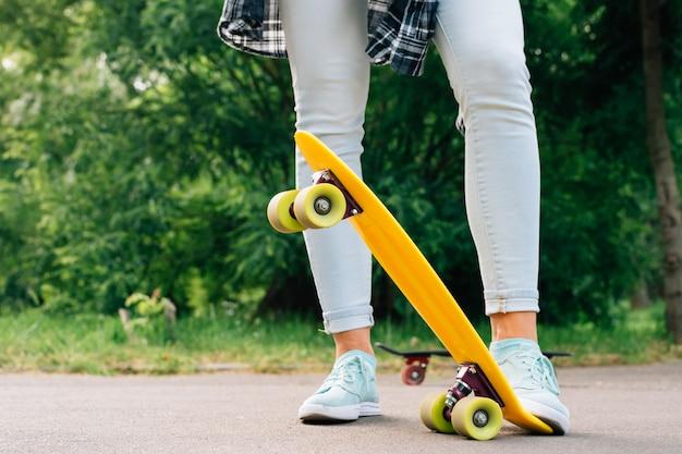 Jambes de femmes en jeans et baskets sur skateboard jaune gros plan Photo Premium