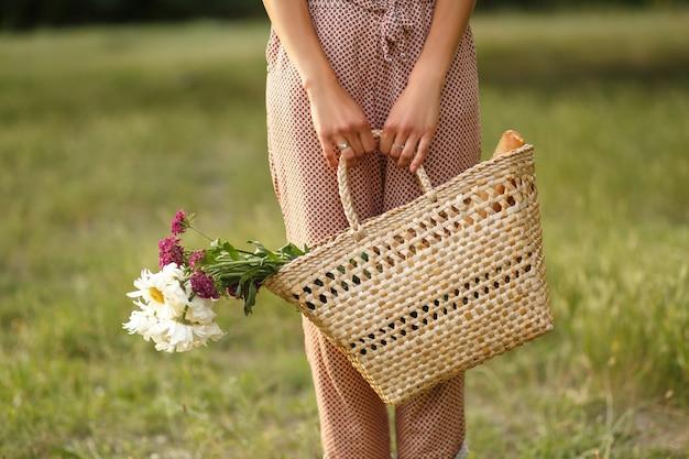 Jambes de femmes avec un panier en osier et des fleurs sur une route de campagne Photo Premium