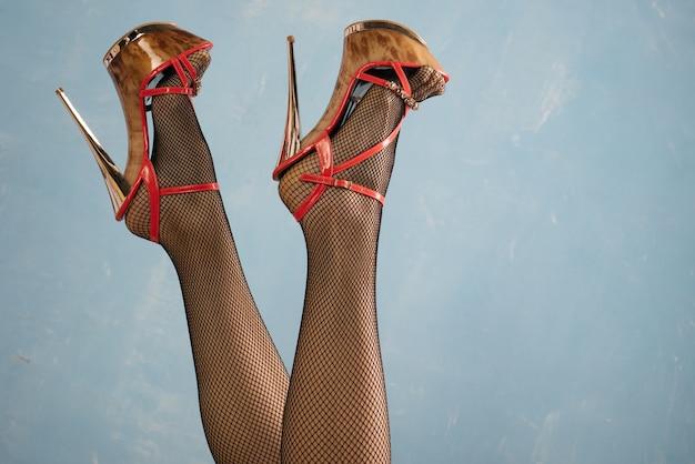 Jambes De Femmes Sexy En Chaussures Noires à Talons Hauts Et Bas Résille Sur Bleu Photo Premium