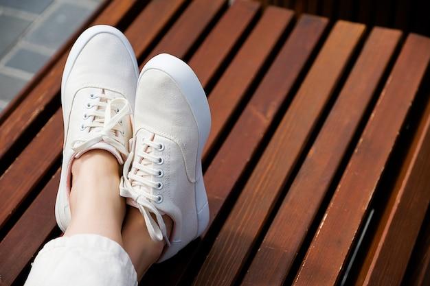 Les jambes de la fille en nouvelles baskets blanches et jeans Photo Premium