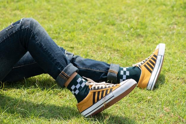 Jambes de l'homme en jeans et baskets jaunes sur l'herbe verte. Photo Premium