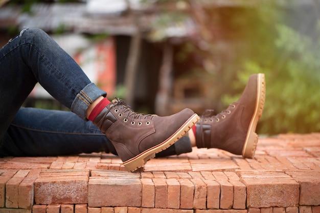 Jambes d'hommes de mode en jeans et bottes marron en cuir pour la collection homme. Photo Premium