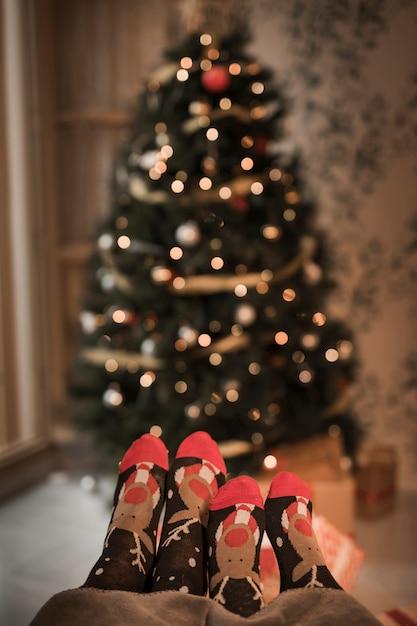 Jambes humaines en chaussettes drôles près de sapin décoré Photo gratuit