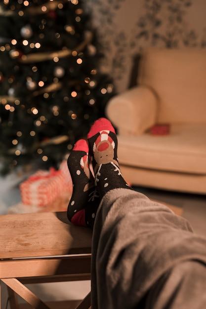 Jambes humaines en chaussettes drôles près de sapin de noël et canapé Photo gratuit