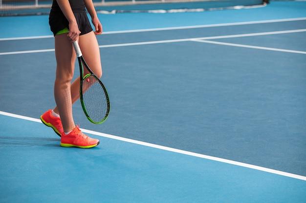 Jambes De Jeune Fille Dans Un Court De Tennis Fermé Avec Balle Et Raquette Photo gratuit