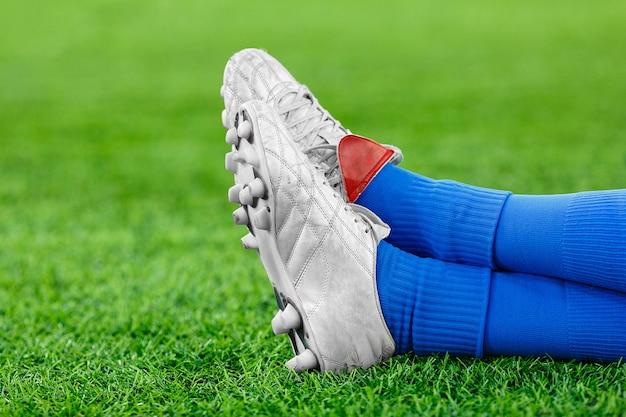 Jambes d'un joueur de football sur une pelouse verte Photo Premium