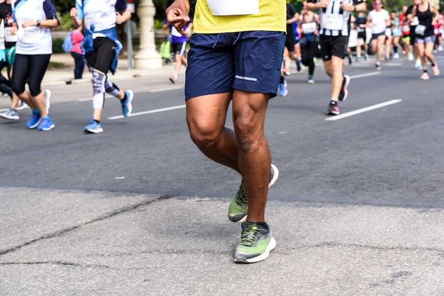 Jambes musclées d'un coureur masculin noir participant à une course amateur dans les rues de valence, en espagne. Photo Premium