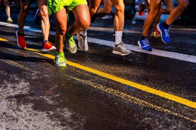 Jambes musclées d'un groupe de plusieurs coureurs s'entraînant sur asphalte Photo Premium