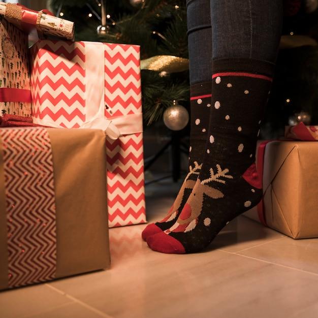 Jambes de la personne en chaussettes de noël entre les boîtes à cadeaux et le sapin décoré Photo gratuit