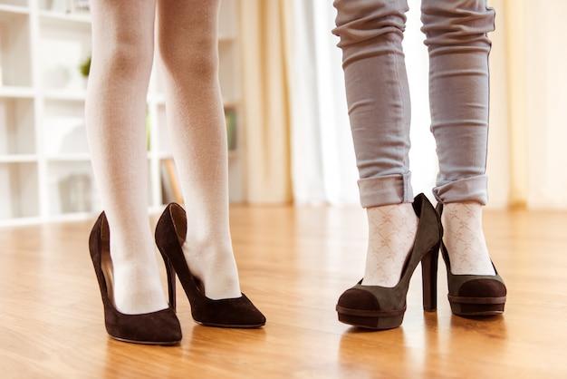 Jambes de petites filles chaussées de grandes chaussures pour femmes adultes. Photo Premium