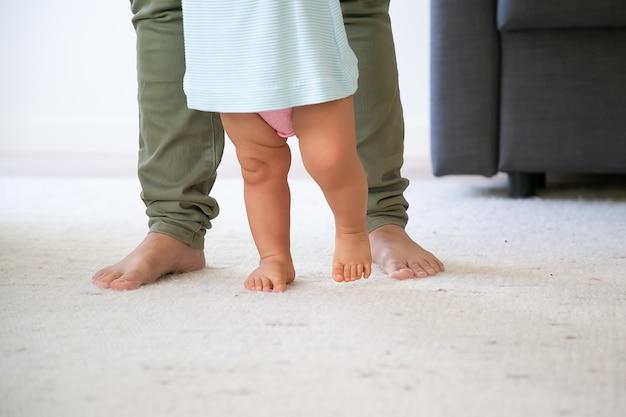 Jambes Pieds Nus Du Bébé Essayant De Marcher Devant Maman. Enfant Faisant Ses Premiers Pas Avec Le Soutien Des Mamans. Photo Recadrée. Concept De Parentalité Et D'enfance Photo gratuit