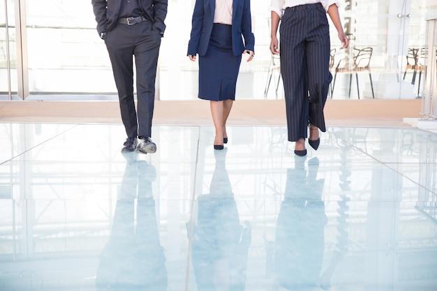 Jambes de trois partenaires d'affaires marchant dans le bureau Photo gratuit
