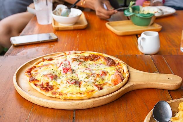 Le jambon pizza sur le plateau en bois est placé sur la table. Photo Premium
