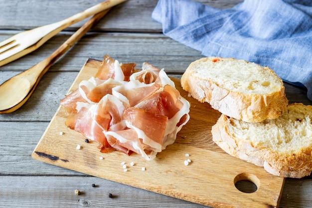 Jambon de prosciutto et pain sur bois Photo Premium