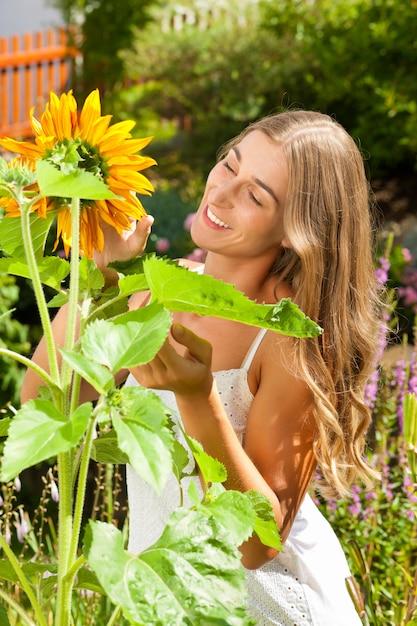 Jardinage En été - Femme Heureuse Avec Des Fleurs Du Soleil Dans Son Jardin Photo Premium