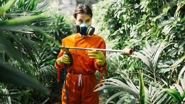 Jardinier femelle pulvérisant un insecticide sur une plante Photo gratuit