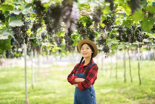 Jardinier heureux de jeunes femmes tenant des branches de raisin bleu mûr Photo gratuit