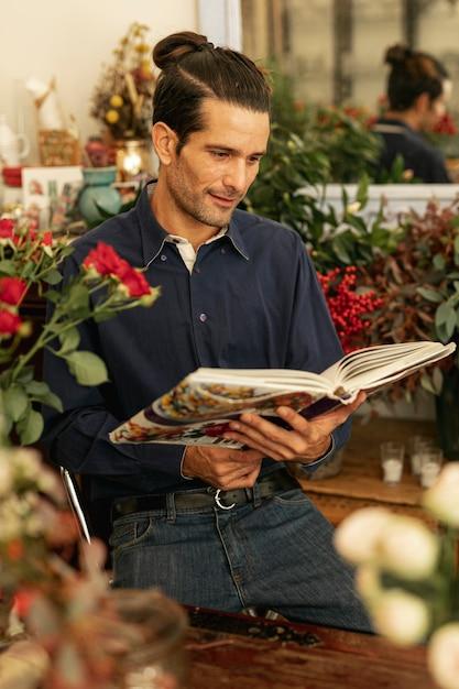 Jardinier Lisant Un Livre Et Entouré De Plantes Photo gratuit