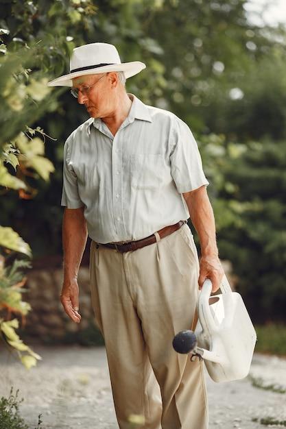 Jardinier Principal Apprécie Son Travail Dans Le Jardin. Vieil Homme En Chemise Blanche. Photo gratuit
