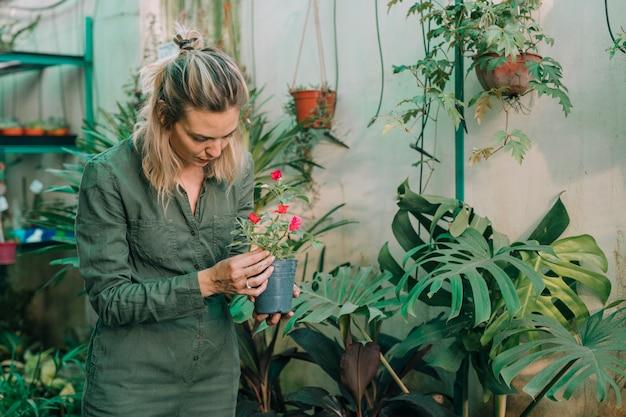 Jardinière blonde prenant soin des plantes à fleurs en pépinière Photo gratuit