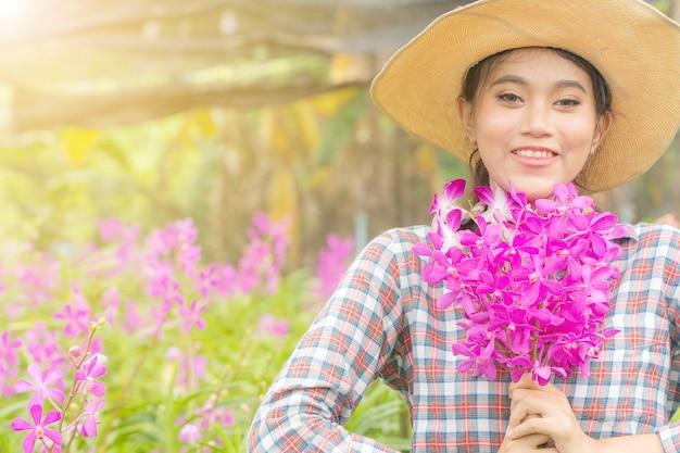 Une jardinière portant une chemise à carreaux coiffée d'un chapeau tient une orchidée rose à la main. Photo Premium