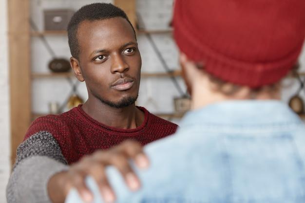 Je Suis Toujours Là Pour Toi. Plan Intérieur D'un Jeune Homme Afro-américain Chaleureux Montrant De La Compassion Envers Un Homme Méconnaissable, Lui Tapotant L'épaule Tout En Essayant De Réconforter Et De Rassurer Son Meilleur Ami Photo gratuit