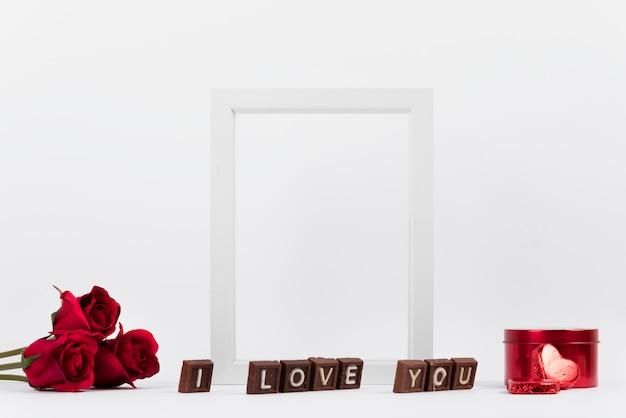 Je t'aime inscription sur des morceaux de chocolat près du cadre photo, des fleurs et une boîte Photo gratuit
