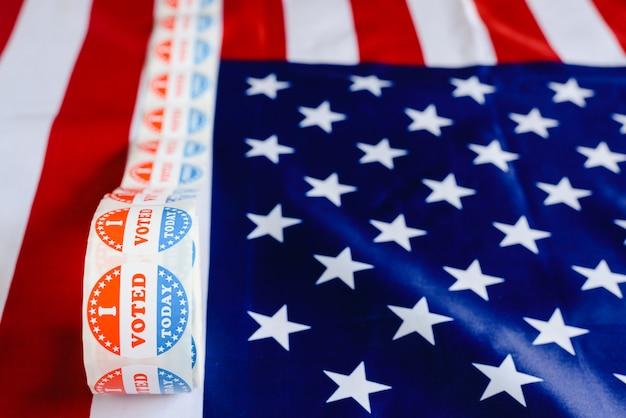 Je vote aujourd'hui sur le rouleau d'autocollants aux élections américaines sur le drapeau américain. Photo Premium