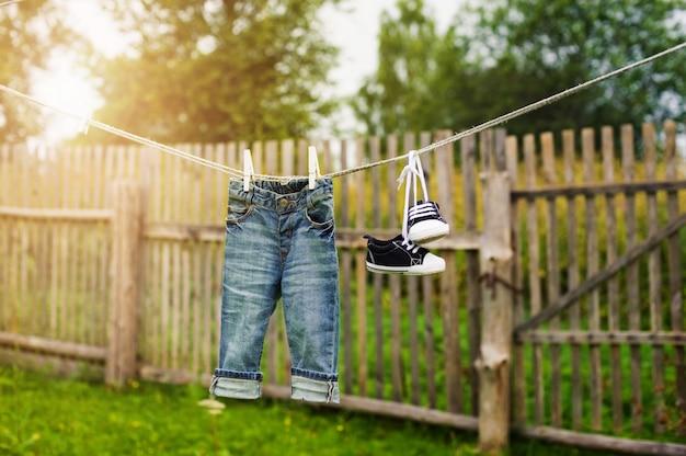 Jeans et baskets pour enfants sur la corde à linge Photo Premium