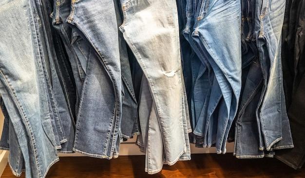 Jeans suspendus sur une grille. rangée de pantalons en denim. concept d'achat, vente, shopping et jeans Photo Premium