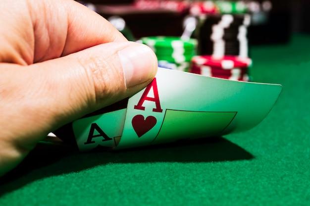Jetons de poker et as de pique et as de cœur sur un tapis vert Photo Premium