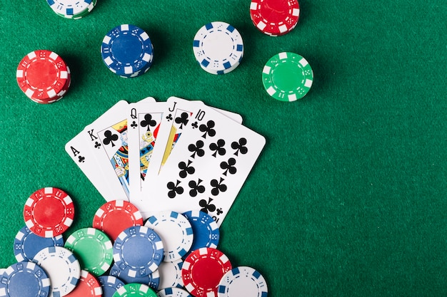 Jetons de poker et club royal flush sur une table de poker verte Photo gratuit