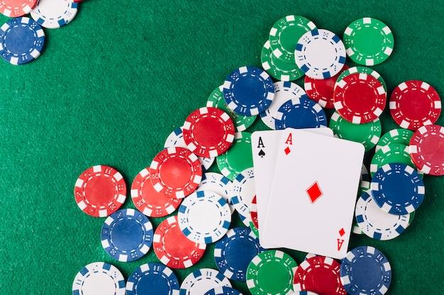 Jetons de poker multicolores et deux cartes à jouer sur fond vert Photo gratuit