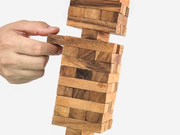 Jeu de jenga de tour de bloc en bois incliné avec la main, concept de risque Photo gratuit