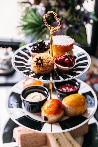 Jeu de pâtisserie pour le thé de l'après-midi avec scones, sandwiches et mini-tartes sur une table en marbre. Photo Premium