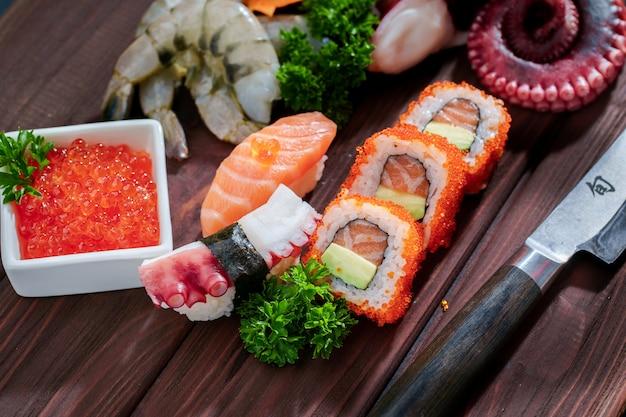 Jeu de sushi. différents sashimis, sushis et rouleaux à la pieuvre Photo Premium